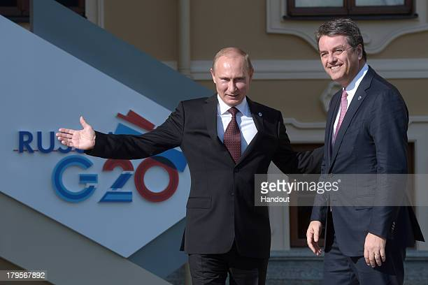 In this handout image provided by Host Photo Agency Russian President Vladimir Putin greets DirectorGeneral of the World Trade Organization Roberto...