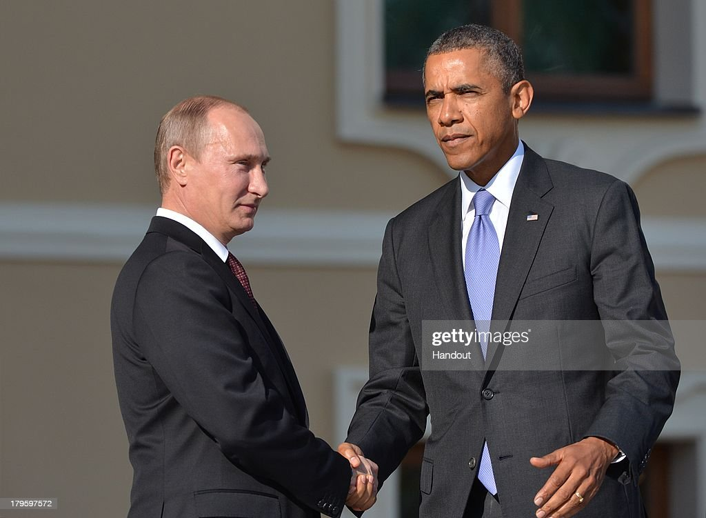 In this handout image provided by Host Photo Agency Russian President Vladimir Putin and US President Barack Obama shake hands during an official...
