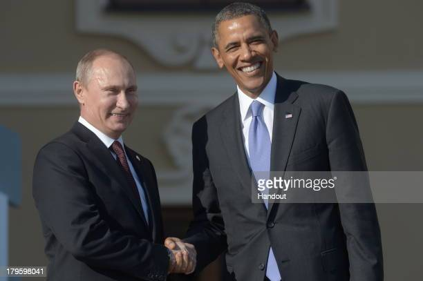 In this handout image provided by Host Photo Agency Russian President Vladimir Putin greets US President Barack Obama during an official welcome of...