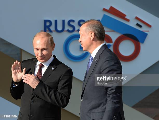 In this handout image provided by Host Photo Agency Russian President Vladimir Putin speaks with and Prime Minister of Turkey Recep Tayyip Erdogan...