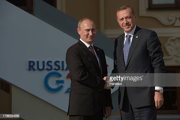 In this handout image provided by Host Photo Agency Russian President Vladimir Putin greets Turkish Prime Minister Tayyip Erdogan at the G20 summit...