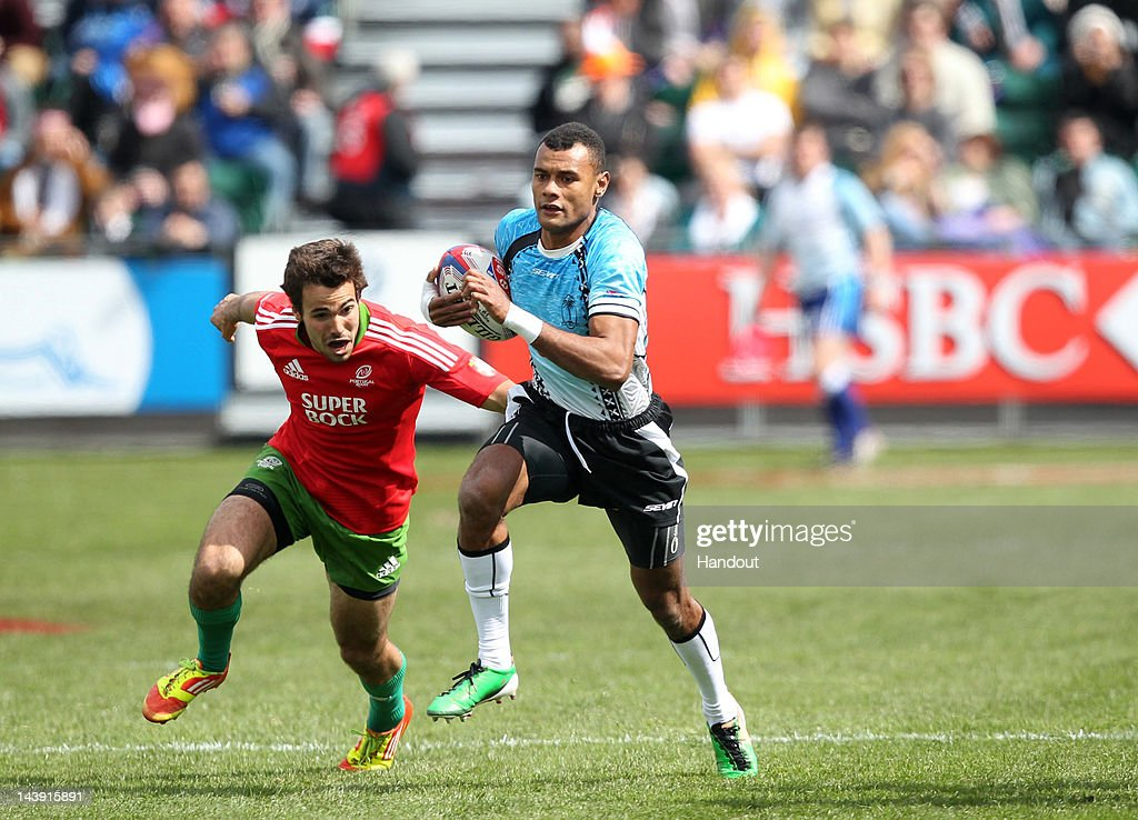 In this handout image provided by HSBC, Joli Baleviani Raqamate (R) of Fiji runs with the ball from Vasco Mendes of Portugal during the HSBC Sevens World Series at Scotstoun Stadium on May 05, 2012 in Glasgow, Scotland.
