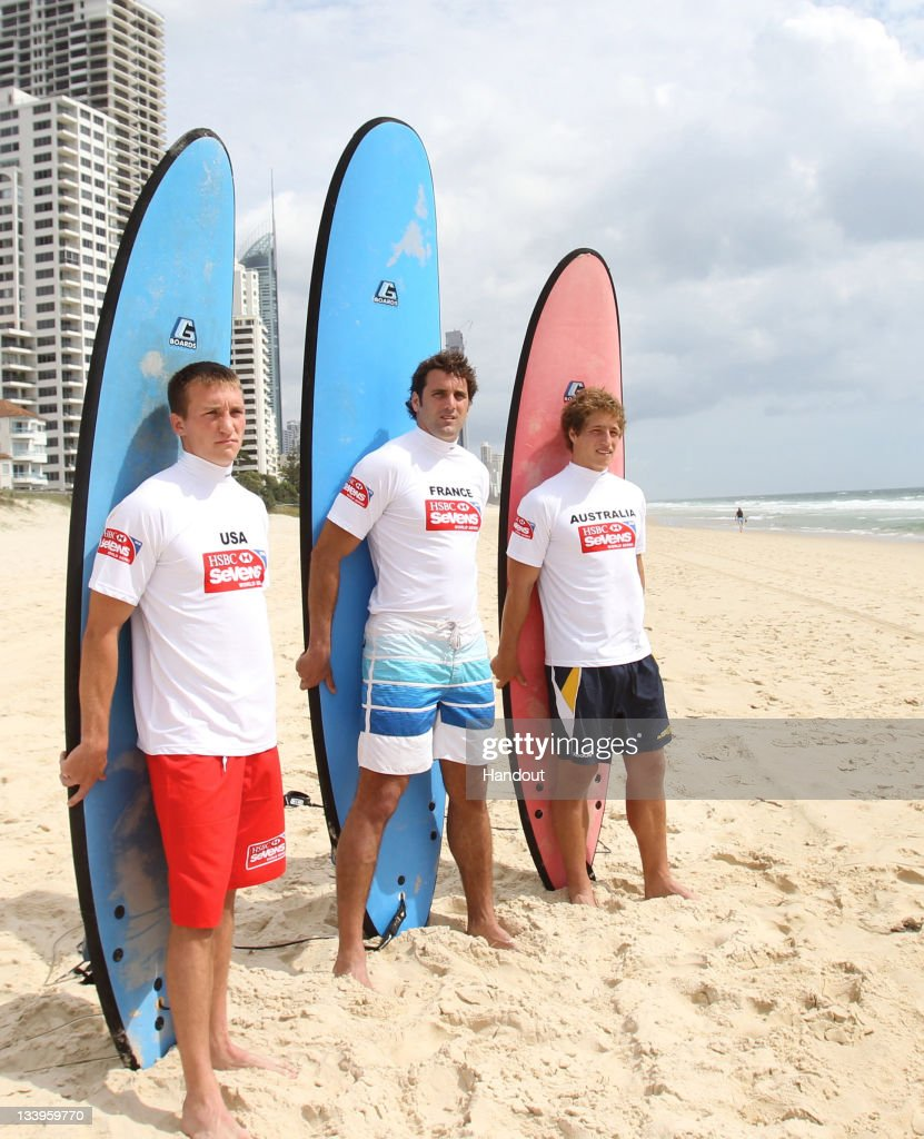 In this handout image provided by HSBC, (L-R) Peter Tiberio of USA, Jean Baptiste Gobelet of France and Jesse Parahi of Australia pose with surfboards at Surfers Paradise beach ahead of the IRB HSBC Sevens World Series on November 23, 2011 in Gold Coast, Australia. (Photo by HSBC via Getty Images).