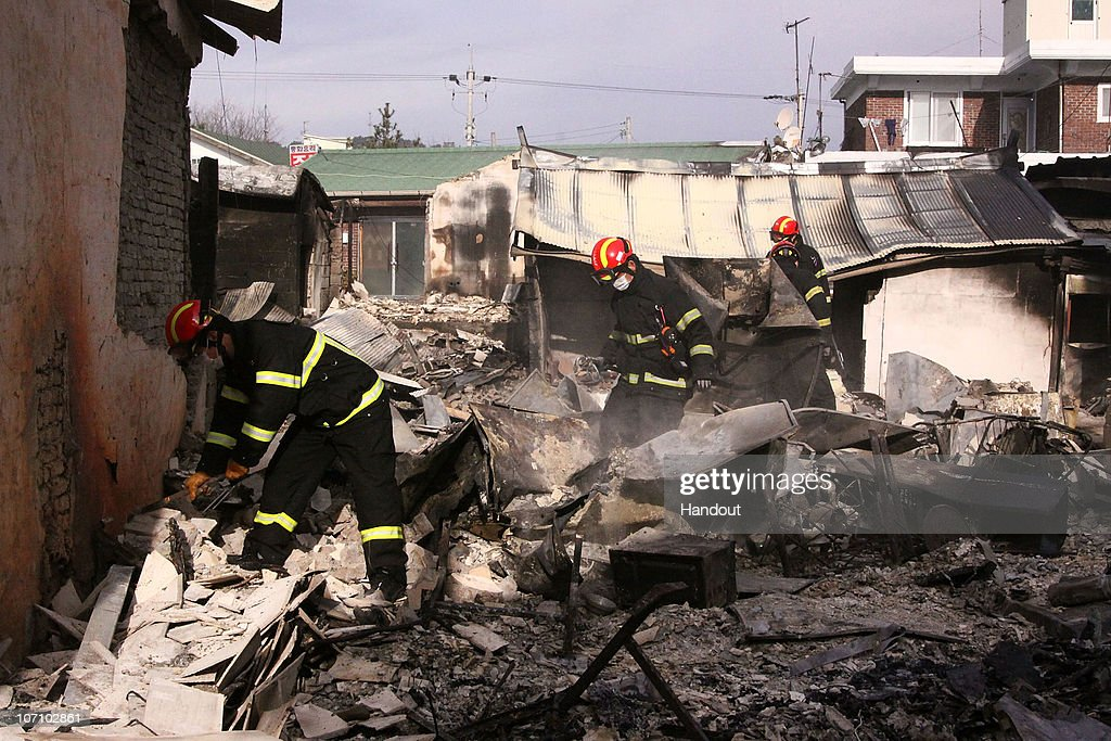 In this handout image provided by Incheon Fire and Safety Management Department firefighters are seen inspecting the damage caused by the artillery...