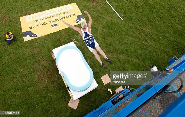 In this handout image provided by James Ram Professor Splash Darren Taylor attempts a world record of diving from 30ft into 12inches of Cornish milk...