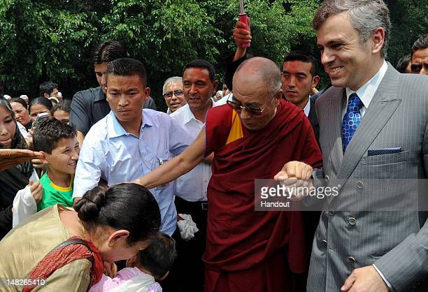 In this handout image provided by Jammu and Kashmir Information Department Tibetan spiritual leader Dalai Lama blesses a woman as he stands with Omar...