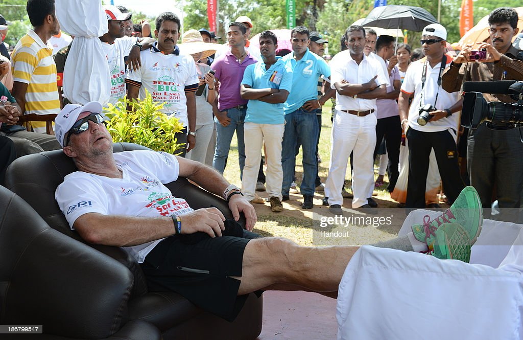 In this handout image provided by Laureus Sir Ian Botham relaxes after the first day of Beefy's Big Sri Lanka walk 2013 walk from Kilinochchi to...