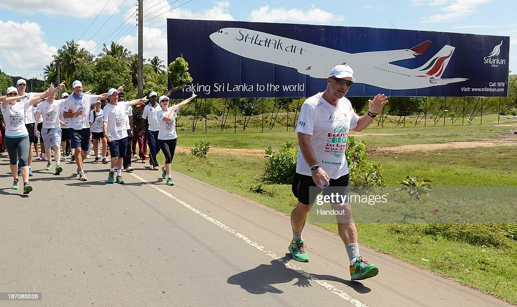 In this handout image provided by Laureus, Sir Ian Botham walks with his team past a hoarding advertising SriLankan Airlines on the sixth day of Beefy's Big Sri Lanka walk 2013 walk on November 6, 2013 from Ranna to Beliatta, Sri Lanka.