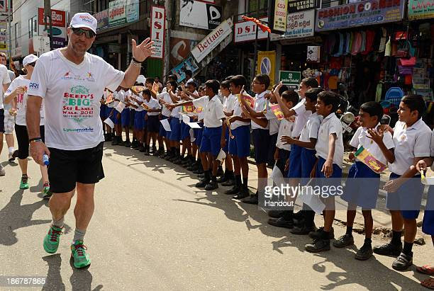 LANKA NOVEMBER 4 In this handout image provided by Laureus Sir Ian Botham waves to children lining the street during the fourth day of Beefy's Big...