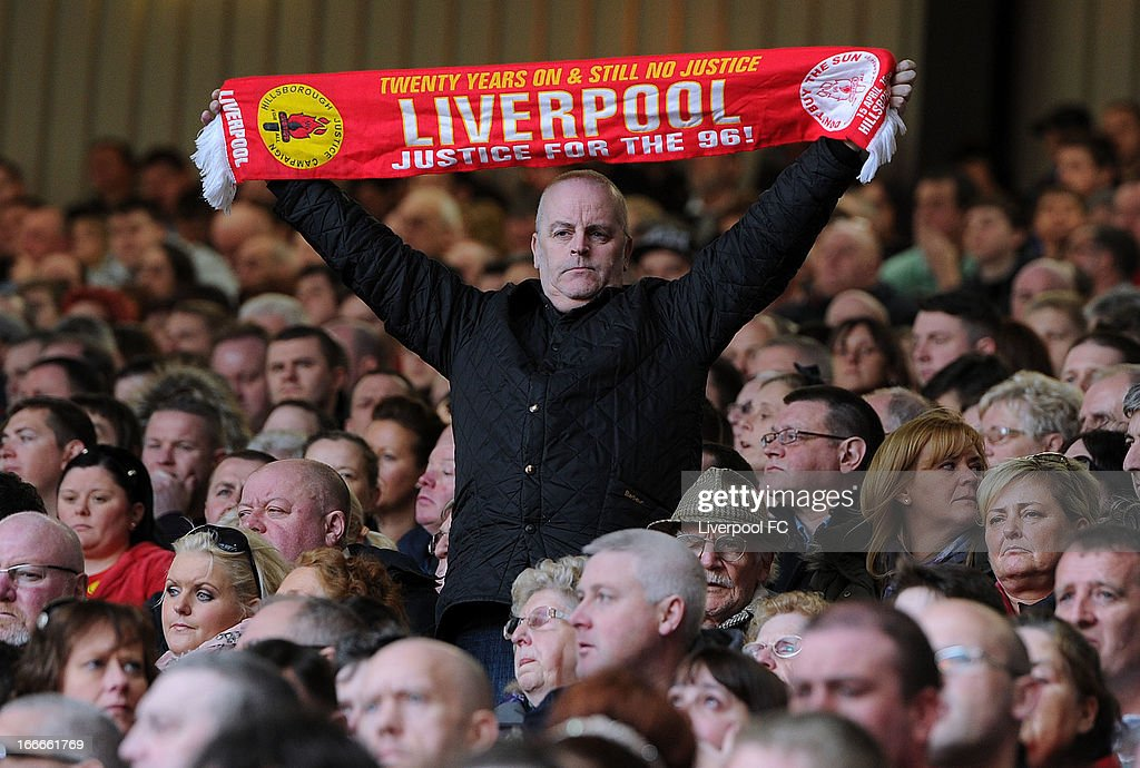 In this handout image provided by Liverpool FC, a member of the congregation stands and holds a scarf aloft at the 24th Hillsborough Anniversary Memorial Service at Anfield on April 15, 2013 in Liverpool, England. Thousands of fans, friends and relatives took part in the service at Liverpool's Anfield Stadium to mark the 24th anniversary of the Hillsborough disaster. A total of 96 Liverpool supporters lost their lives during a crush at an FA Cup semi final against Nottingham Forest at the Hillsborough football ground in Sheffield, South Yorkshire in 1989.