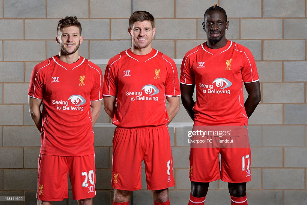 In this handout image provided by Liverpool FC, (L-R) <a gi-track='captionPersonalityLinkClicked' href=/galleries/search?phrase=Adam+Lallana&family=editorial&specificpeople=5475862 ng-click='$event.stopPropagation()'>Adam Lallana</a>, <a gi-track='captionPersonalityLinkClicked' href=/galleries/search?phrase=Steven+Gerrard&family=editorial&specificpeople=202052 ng-click='$event.stopPropagation()'>Steven Gerrard</a> and <a gi-track='captionPersonalityLinkClicked' href=/galleries/search?phrase=Mamadou+Sakho&family=editorial&specificpeople=4154099 ng-click='$event.stopPropagation()'>Mamadou Sakho</a> pose wearing the Liverpool shirt with the new logo 'Seeing Is Believing' on February 10, 2015 in Liverpool, England.
