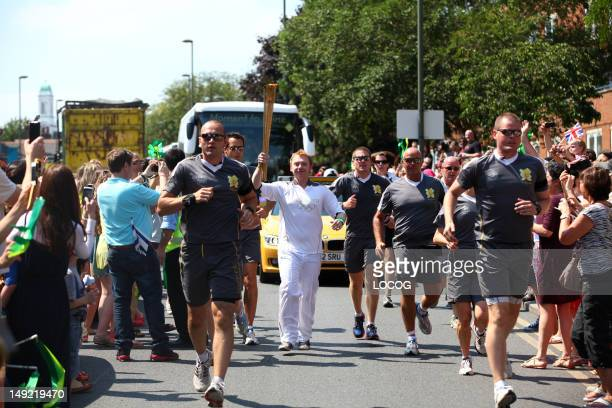 In this handout image provided by LOCOG Actor Torchbearer 060 Rupert Grint carries the Olympic Flame on the Torch Relay leg through Barnet during Day...