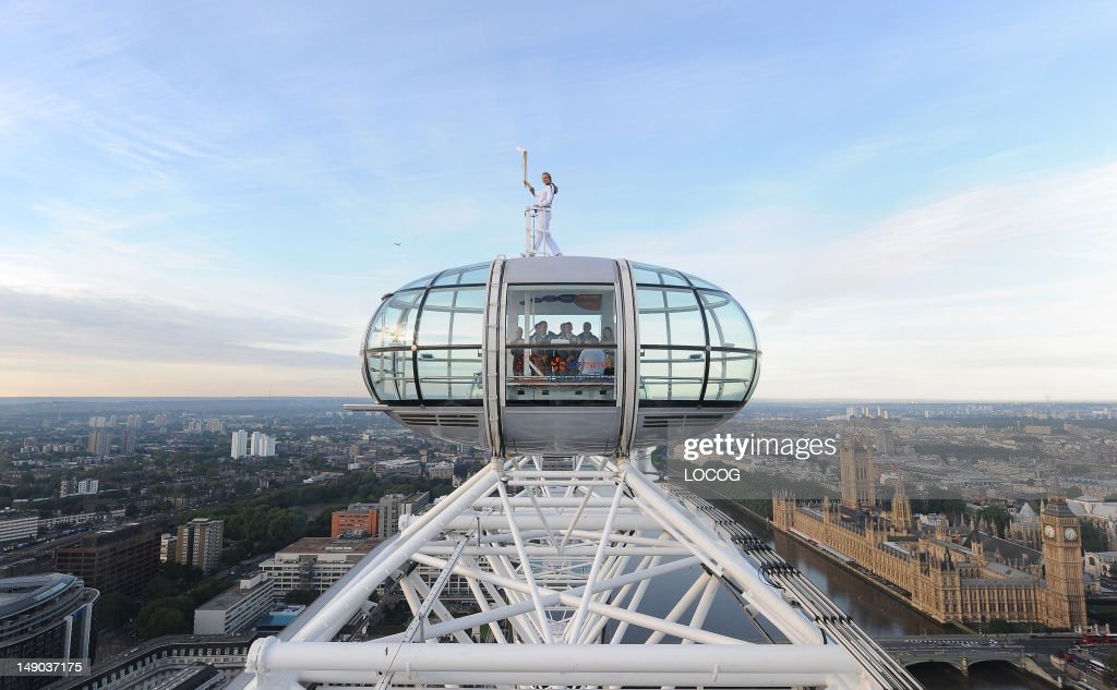 In this handout image provided by LOCOG, Amelia Hempleman-Adams poses with the Olympic Flame on top of a London Eye pod during Day 65 of the London 2012 Olympic Torch Relay on July 22, 2012 in London, England. The Olympic Flame is now on day 63 of a 70-day relay involving 8,000 torchbearers covering 8,000 miles.