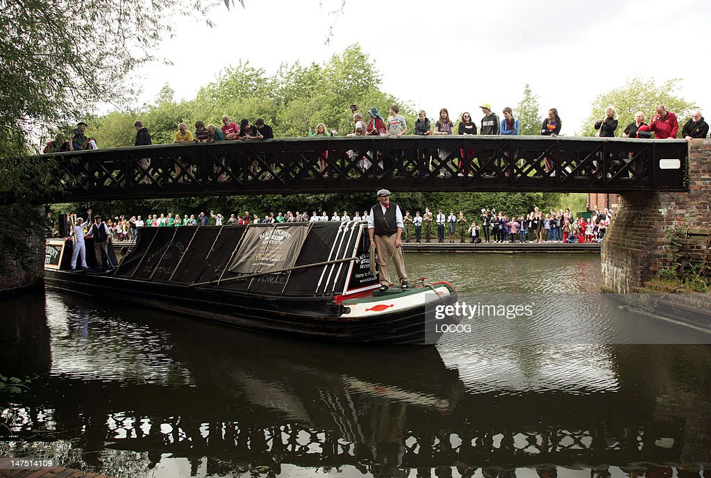 In this handout image provided by LOCOG Dennis Sanders carries the Olympic Flame on the Black Country Living Museum longboat on the Torch Relay leg...