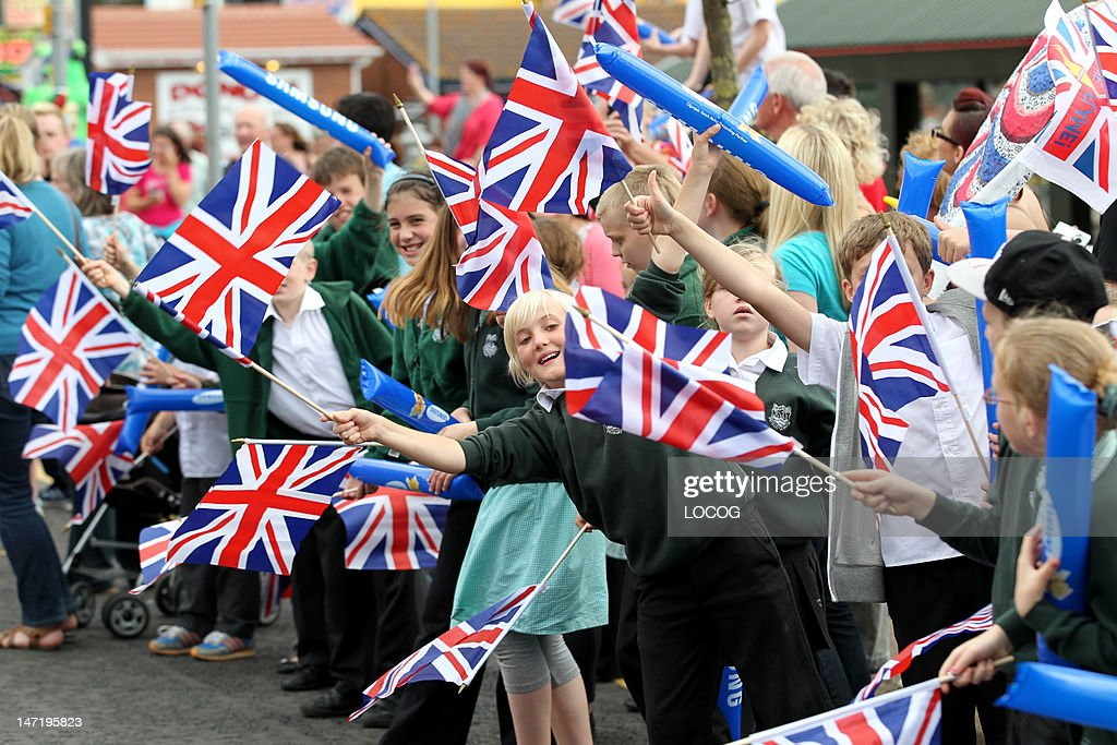 In this handout image provided by LOCOG, Local schoolchildren wave Union Jack flags on the streets of Skegness during Day 40 of the London 2012 Olympic Torch Relay on June 27, 2012 in Skegness, England. The Olympic Flame is now on day 40 of a 70-day relay involving 8,000 torchbearers covering 8,000 miles.