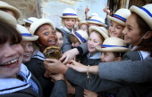 In this handout image provided by LOCOG Schoolgirls from Leadenhall School hold the Olympic Torch of Olympic gold medalist former sprinter...