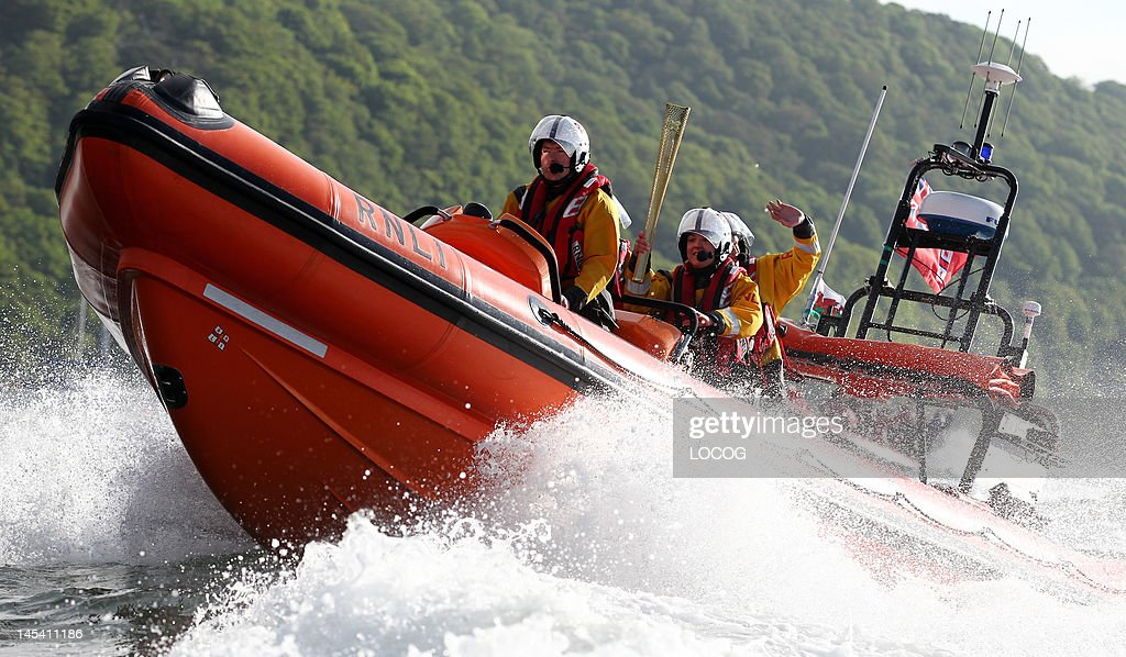 In this handout image provided by LOCOG The Beaumaris RNLI lifeboat crew assist Olympic Torchbearer Elen Evans as she carries the Olympic Flame...