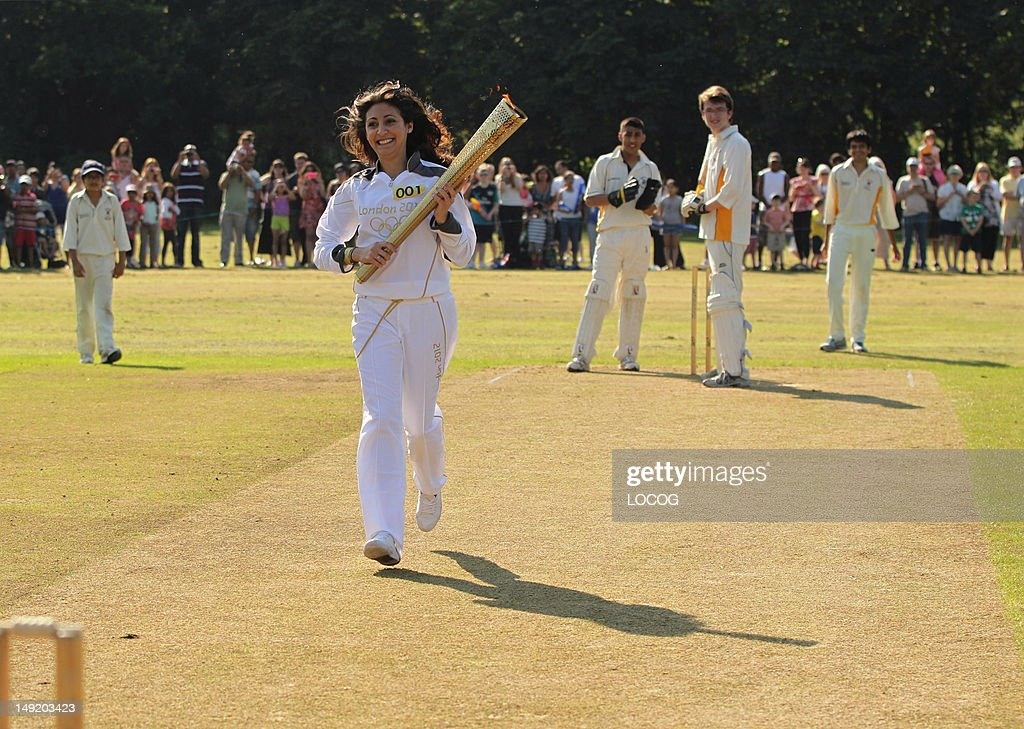 In this handout image provided by LOCOG, Torchbearer 001 Joanna Hyams carries the Olympic Flame on the wicket at Pinner Cricket Club in Harrow at the beginning of Day 68 of the London 2012 Olympic Torch Relay on July 25, 2012 in London, England. The Olympic Flame is now on Day 68 of a 70-day relay involving 8,000 torchbearers covering 8,000 miles.