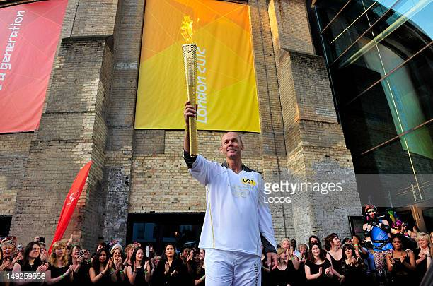 In this handout image provided by LOCOG Torchbearer 001 Sir Clive Woodward holds the Olympic Flame at the Camden Roundhouse in Camden at the...