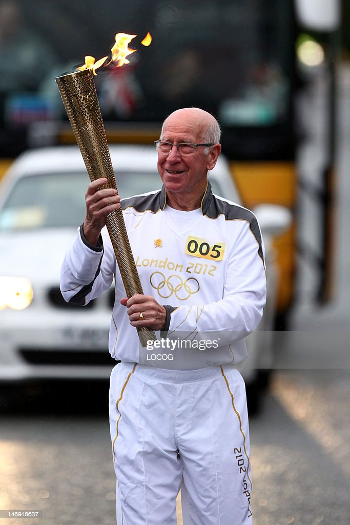 In this handout image provided by LOCOG, Torchbearer 005 Sir Bobby Charlton carries the Olympic Flame on the Torch Relay leg between Salford and Moss Side on Day 37 of the London 2012 Olympic Torch Relay on June 24, 2012 in Manchester, England. The Olympic Flame is now on day 37 of a 70-day relay involving 8,000 torchbearers covering 8,000 miles.
