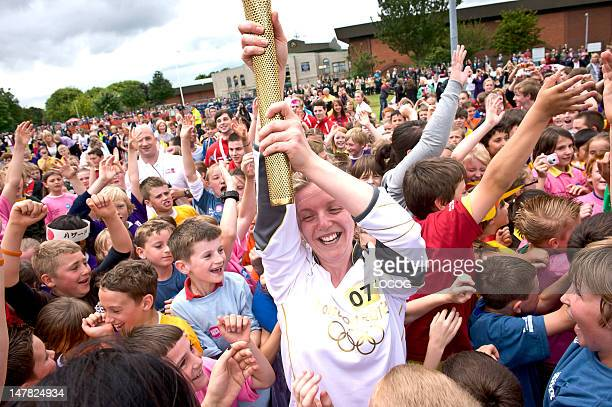 In this handout image provided by LOCOG Torchbearer 071 Lauren Reeder holds the Olympic Flame surrounded by local children on the running track at...