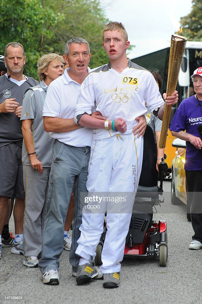 In this handout image provided by LOCOG, Torchbearer 075 Jack Mitchell is assisted out of his wheelchair as he walks the last part of his leg carrying the Olympic Flame during Day 38 of the London 2012 Olympic Torch Relay on June 25, 2012 in Pontefract, England. The Olympic Flame is now on day 38 of a 70-day relay involving 8,000 torchbearers covering 8,000 miles.
