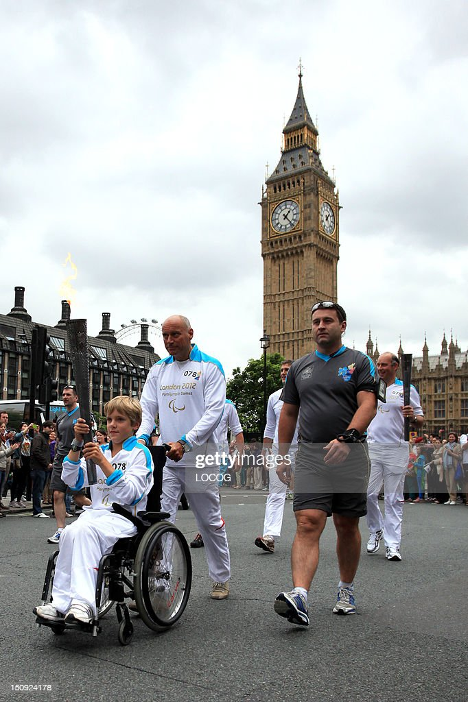 In this handout image provided by LOCOG, Torchbearer 078 Edward Parker carries the Paralympic Flame through Parliament Square on the Torch Relay leg across London, on August 29, 2012 in England.