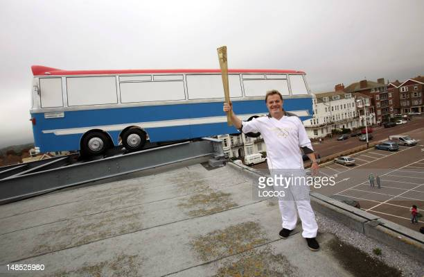 In this handout image provided by LOCOG Torchbearer 117 Eddie Izzard holds the Olympic Torch in front of The Italian Job inspired instillation 'Hang...