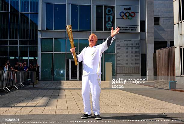 In this handout image provided by LOCOG Torchbearer 131 Sir Bruce Forsyth carries the Olympic Flame on the Torch Relay leg through Kensington and...