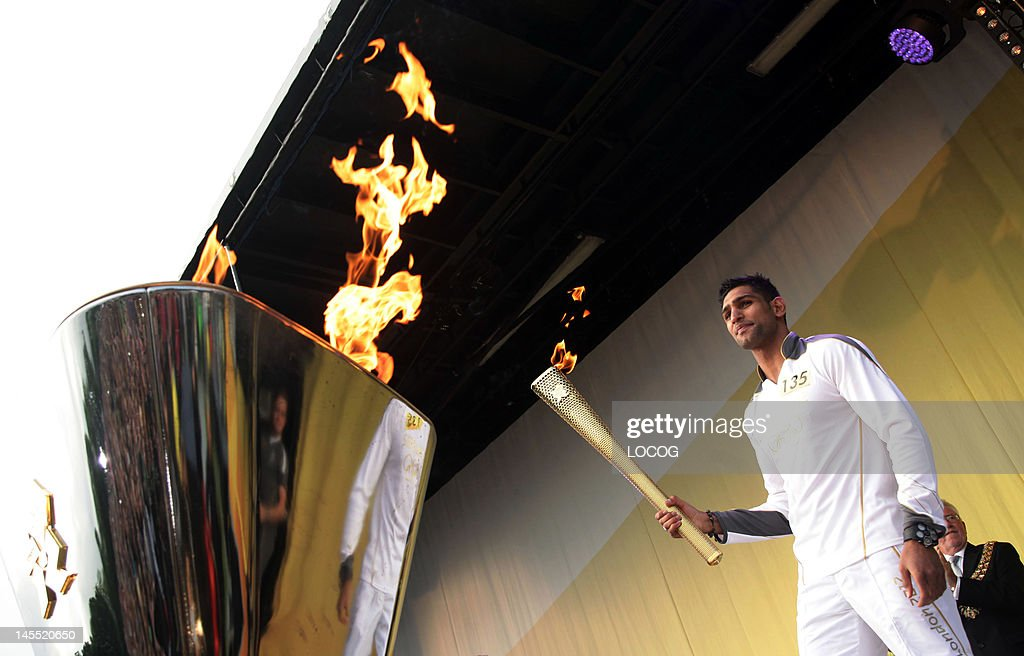 In this handout image provided by LOCOG Torchbearer Amir Khan lights the cauldron with the Olympic Flame at the end of the Torch Relay leg through...