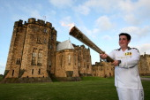In this handout image provided by LOCOG Torchbearer Lewis Denny carries the Olympic Flame through the grounds of Alnwick Castle which was used in the...