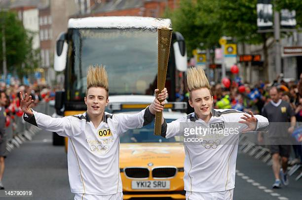 In this handout image provided by LOCOG Torchbearers 007 John and Edward Grimes aka Jedward carry the Olympic Flame on day 19 of the London 2012...