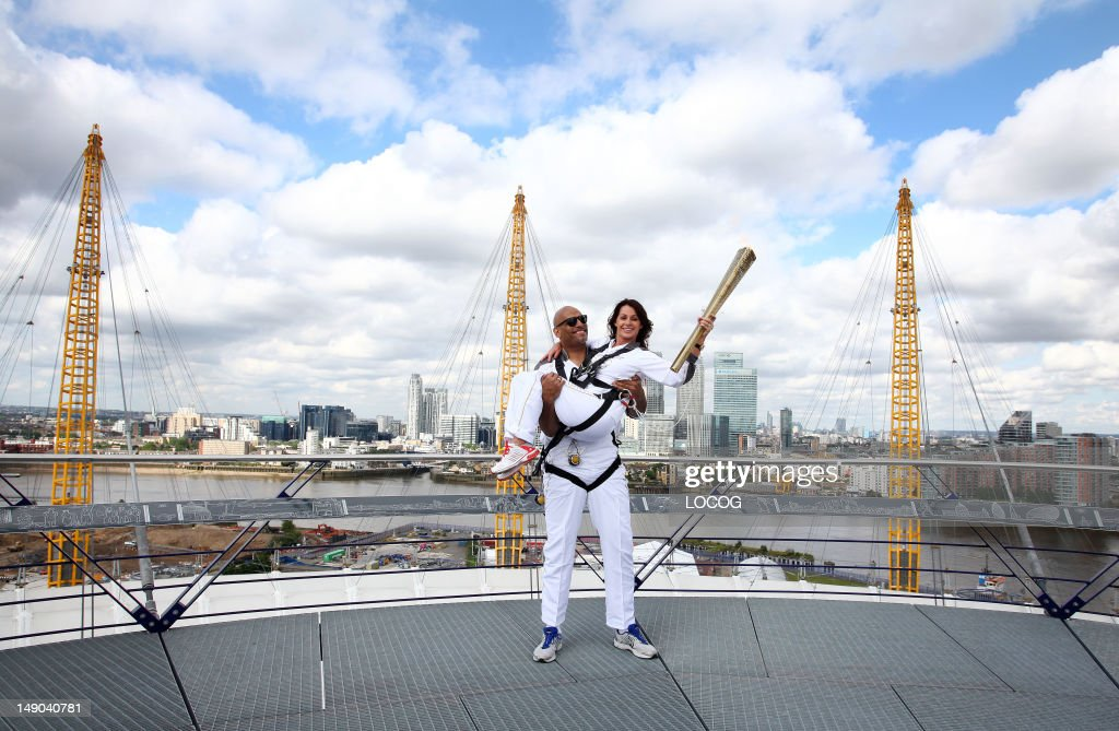 In this handout image provided by LOCOG, Torchbearers John Amaechi and Nadia Comaneci (R) pose with the Olympic Torch on the viewing platform of the North Greenwich Arena during Day 64 of the London 2012 Olympic Torch Relay on July 21, 2012 in London, England. The Olympic Flame is now on Day 64 of a 70-day relay involving 8,000 torchbearers covering 8,000 miles.