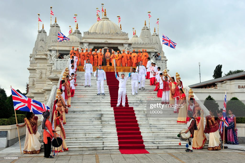 In this handout image provided by LOCOG, Torchbearing team 056 Barrie Guy, Antony Eames, and others (no names available) pose for photographs outside the Shri Swaminarayan Mandir temple in Neasden, as they carry the Paralympic Flame during the Torch Relay leg through Brent on August 29, 2012 in London, England.