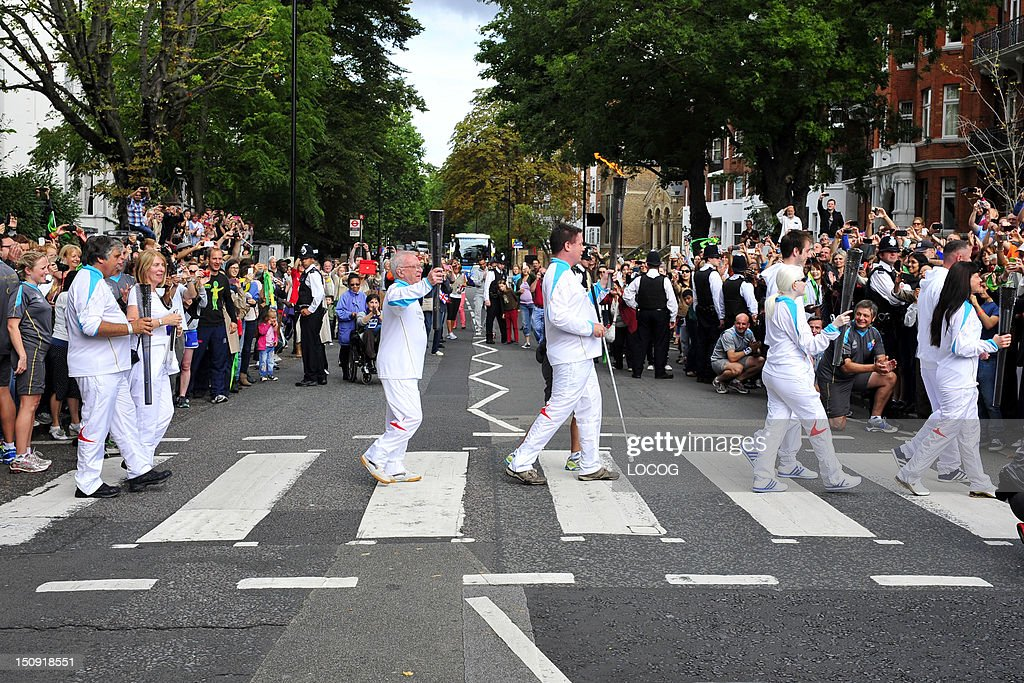 In this handout image provided by LOCOG, Torchbearing team 067 Lucy Priest, Ketaki Vaidya, Kenneth Maidens, Graham Helm, Christopher Tattersall cross the Abbey Road zebra crossing, as they carry the Paralympic Flame on the Torch Relay leg across London, on August 29, 2012 in England.