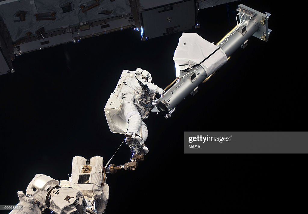In this handout image provided by NASA, anchored to a Canadarm2 mobile foot restraint, NASA astronaut Garrett Reisman, STS-132 mission specialist, participates in the mission's first session of extravehicular activity (EVA) as construction and maintenance continue on the International Space Station on May 17, 2010 in space. During the seven-hour, 25-minute spacewalk, Reisman and NASA astronaut Steve Bowen (out of frame), mission specialist, loosened bolts holding six replacement batteries, installed a second antenna for high-speed Ku-band transmissions and adding a spare parts platform to Dextre, a two-armed extension for the station's robotic arm.This is the final scheduled mission for Atlantis and it will dock with the International Space Station to deliver a payload of a new Russian compartment and fresh batteries.