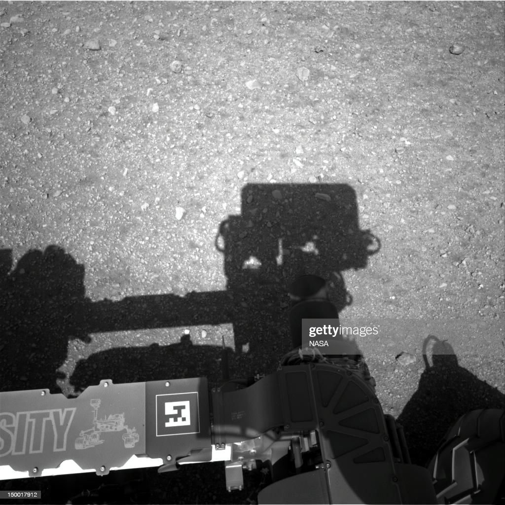 In this handout image provided by NASA and released on August 8, 2012, is the first image taken by the Navigation cameras on NASA's Curiosity rover. It shows the shadow of the rover's now-upright mast in the center, and the arm's shadow at left. The arm itself can be seen in the foreground. The navigation camera is used to help find the sun -- information that is needed for locating, and communicating, with Earth. After the camera pointed at the sun, it turned in the opposite direction and took this picture. The position of the shadow helps confirm the sun's location.