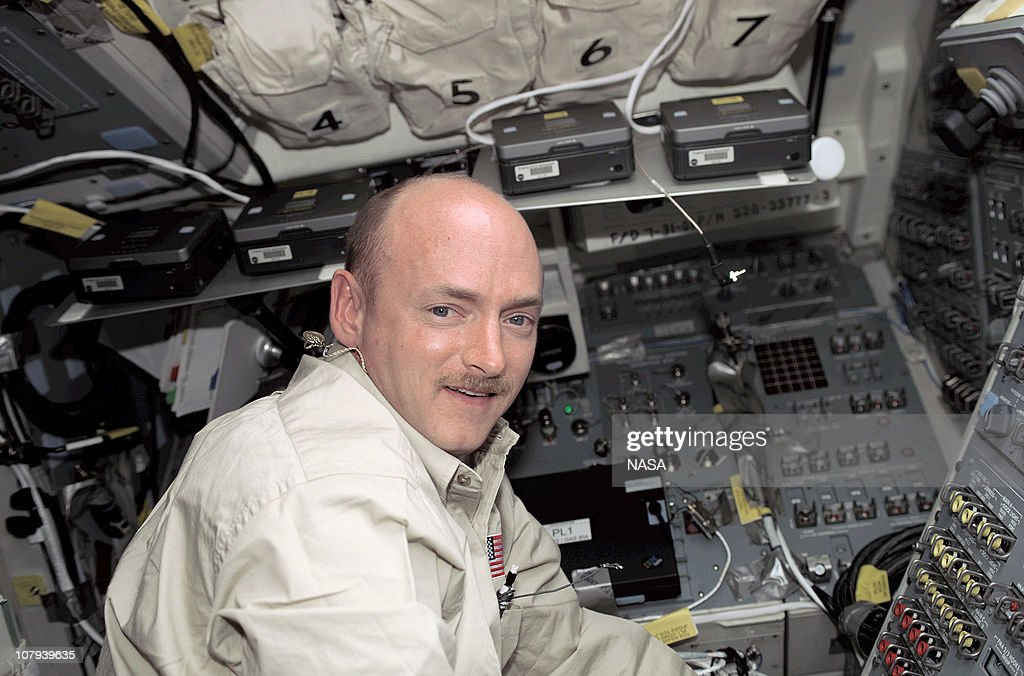 In this handout image provided by NASA astronaut Mark E Kelly STS108 pilot stands at the aft flight deck control panel on the Space Shuttle Endeavour...