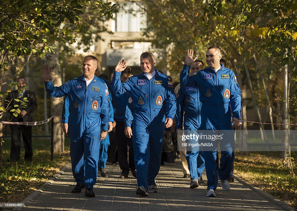 In this handout image provided by NASA, Expedition 33/34 crew members, Flight Engineer Kevin Ford of NASA (L), Soyuz Commander Oleg Novitskiy, and Flight Engineer Evgeny Tarelkin of ROSCOSMOS (R), depart the Cosmonaut Hotel to head to another building across the Baikonur Cosmodrome where they will suit-up for their soyuz launch, on October 23, 2012, in Baikonur, Kazakhstan. Launch of the Soyuz rocket will send Ford, Novitskiy and Tarelkin on a five-month mission aboard the International Space Station.