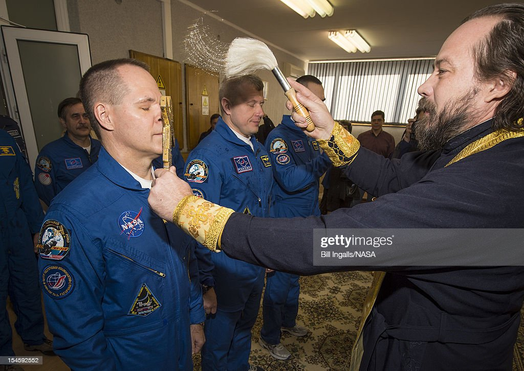In this handout image provided by NASA, Expedition 33/34 crew members, Flight Engineer Kevin Ford of NASA (L), Soyuz Commander Oleg Novitskiy, and Flight Engineer Evgeny Tarelkin of ROSCOSMOS (R), receive the traditional blessing from a Russian Orthodox priest at the Cosmonaut Hotel on the morning of their Soyuz launch to the International Space Station on October 23, 2012, in Baikonur, Kazakhstan. Launch of the Soyuz rocket will send Ford, Novitskiy and Tarelkin on a five-month mission aboard the International Space Station.