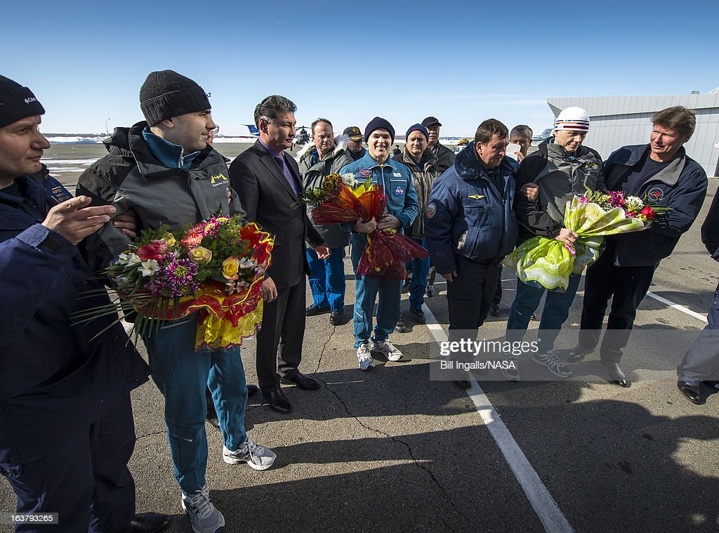In this handout image provided by NASA, (L-R with flowers) Expedition 34 Russian Flight Engineer Evgeny Tarelkin, Flight Commander Kevin Ford of NASA, and Russian Soyuz Commander Oleg Novitskiy are greeted at the Kostanay Airport a few hours after they landed on March 16, 2013 near the town of Kostanay, Kazakhstan. Ford, Novitskiy, and Tarelkin are returning from 142 days onboard the International Space Station where they served as members of the Expedition 33 and 34 crews.