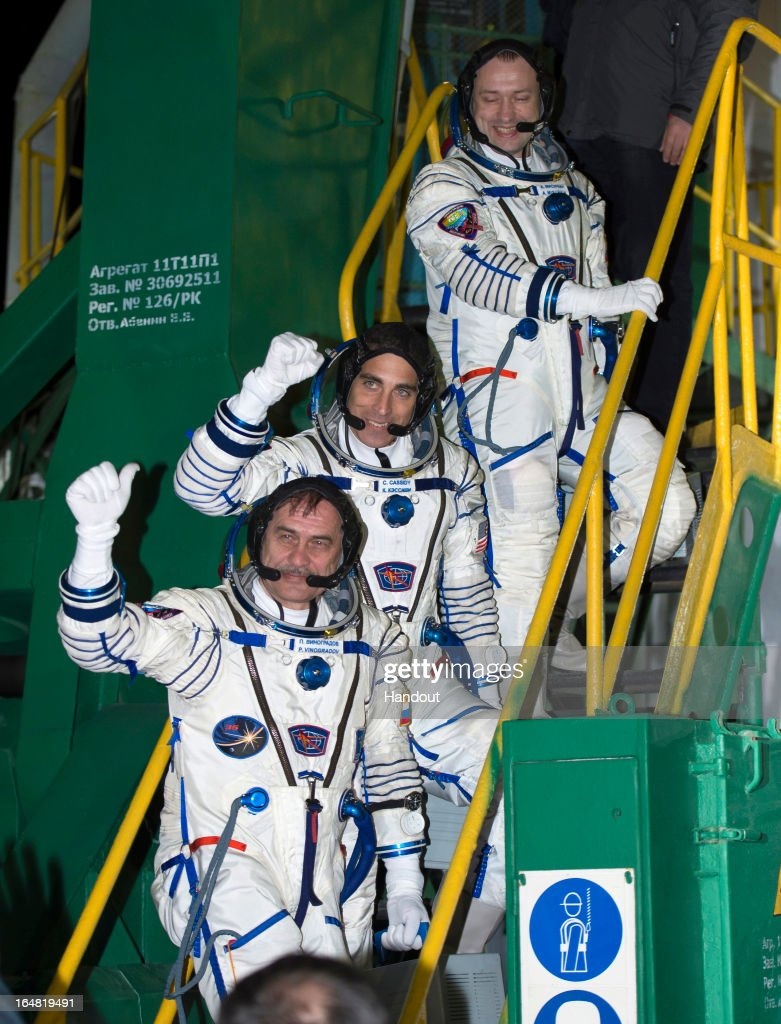 In this handout image provided by NASA, (R-L) Expedition 35 Russian Flight Engineer Aleksandr Misurkin, NASA Flight Engineer Chris Cassidy, and Soyuz Commander Pavel Vinogradov, wave farewell from the base of the Soyuz rocket at the Baikonur Cosmodrome March 29, 2013 in Baikonur, Kazakhstan. Their Soyuz TMA-08M rocket launched at 2:43 a.m. local time to transport the crew to the International Space Station.