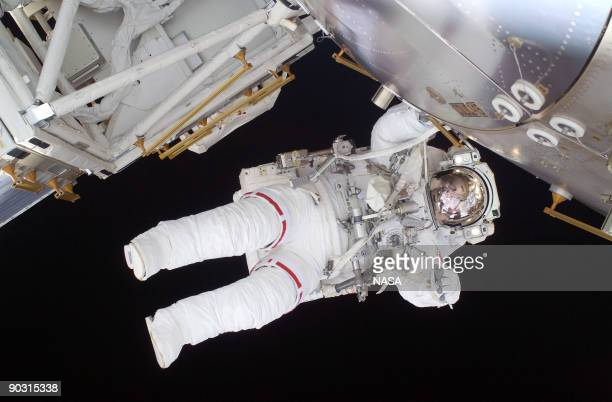 In this handout image provided by NASA flight engineer Nicole Stott of the space shuttle Discovery works during a sixandahalf hour spacewalk...