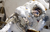 In this handout image provided by NASA NASA astronaut Alvin Drew waves as he participates in the mission's first session of extravehicular activity...