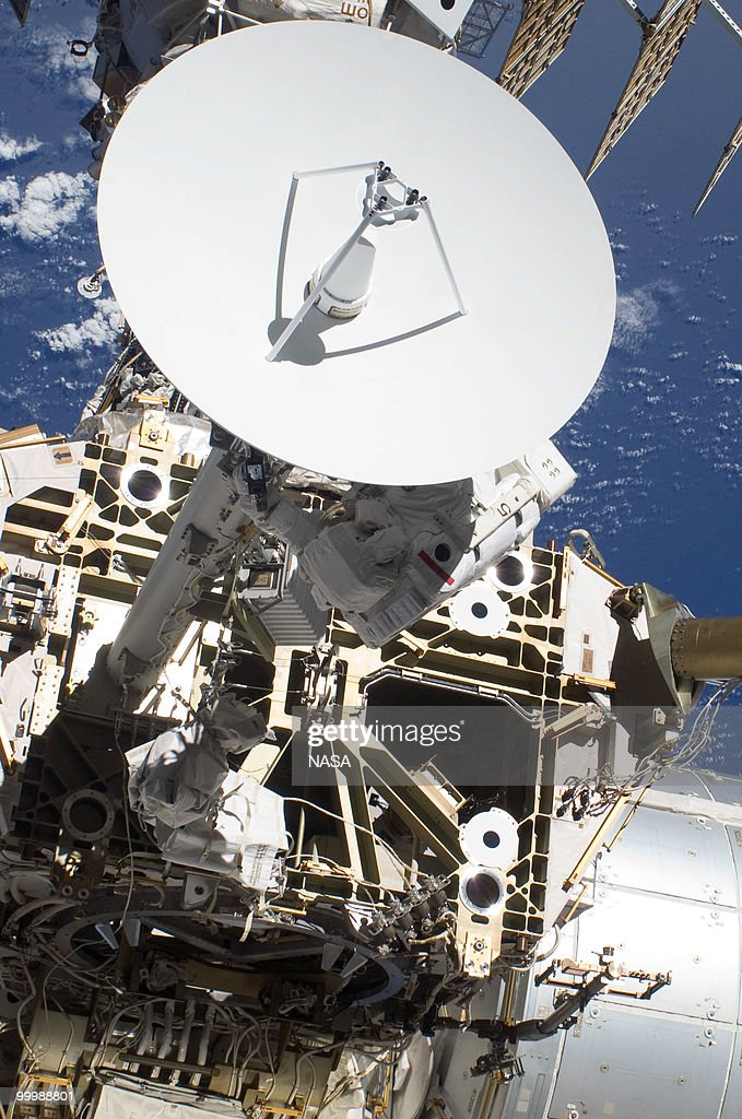 In this handout image provided by NASA, NASA astronaut Steve Bowen (partially obscured by Ku-band antenna), STS-132 mission specialist, participates in the mission's first session of extravehicular activity (EVA) as construction and maintenance continue on the International Space Station on May 17, 2010 in space. During the seven-hour, 25-minute spacewalk, Reisman and NASA astronaut Steve Bowen, mission specialist, loosened bolts holding six replacement batteries, installed a second antenna for high-speed Ku-band transmissions and adding a spare parts platform to Dextre, a two-armed extension for the station's robotic arm.This is the final scheduled mission for Atlantis and it will dock with the International Space Station to deliver a payload of a new Russian compartment and fresh batteries.