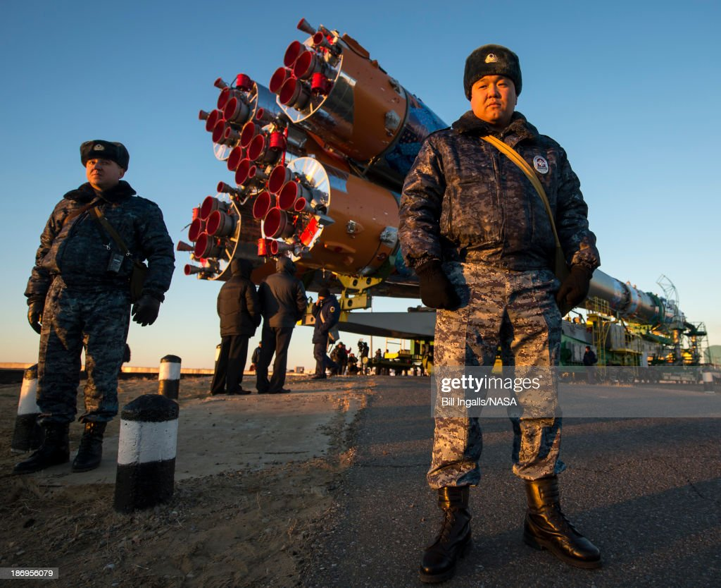 In this handout image provided by NASA Security monitors the Soyuz TMA11M rocket adorned with the logo of the Sochi Olympic Organizing Committee and...