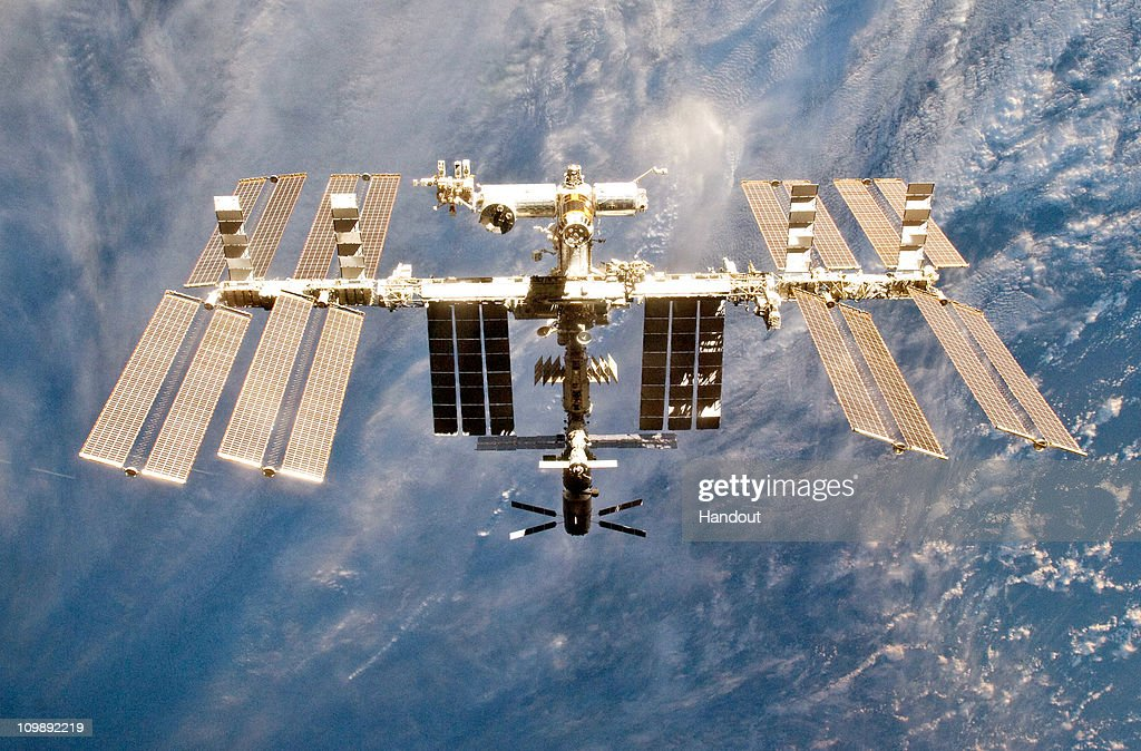 In this handout image provided by NASA the International Space Station is seen from the space shuttle Discovery as the two orbital spacecraft...