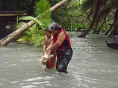 In this handout image provided by Plan International Australia a woman and boy carry a pig through flood waters March 13 2015 on the island of Tuvalu...