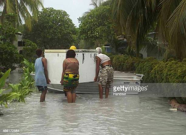 In this handout image provided by Plan International Australia residents rescue belongings as flood waters move inland on March 14 2015 on the island...