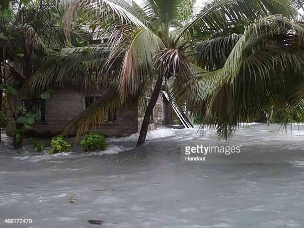 In this handout image provided by Plan International Australia flood waters move inland on March 14 2015 on the island of Tuvalu Cyclone Pam is...